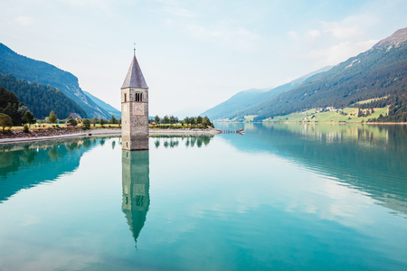The old bell tower of Curon Venosta church rising out of the waters lake of Resia, Graun im Vinschgau village, Trentino-Alto Adige region of Italy, Europe. Gorgeous scene. Explore the world's beauty.