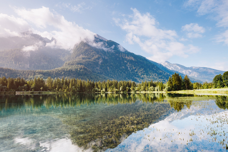 Famous Hintersee lake at sunny day. Picturesque scene. Wonderful natural background. Location resort Ramsau, National park Berchtesgadener Land, Upper Bavaria, Germany Alps, Europe. World of beauty. Stock Photo