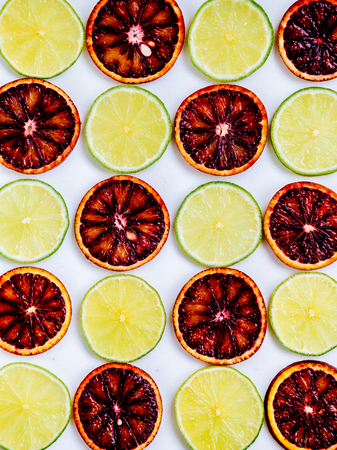 Red orange and lime fruits isolated on white background. Natural organic concept. Symmetrical arrangement, flat lay styling. Top view. Creative still life idea of spring wallpaper. Art photography. Stock Photo
