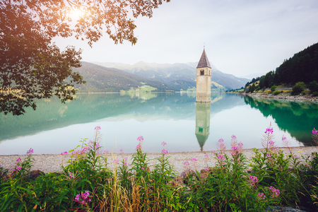 The old bell tower of Curon Venosta church rising out of the waters lake of Resia, Graun im Vinschgau village, Trentino-Alto Adige region of Italy, Europe. Gorgeous scene. Explore the worlds beauty.