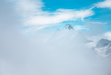 Great view of the snow spire through thick fog. Dramatic and gorgeous scene. Location place Swiss alps, Grindelwald valley, Bernese Oberland, Europe. Artistic picture. Discover the world of beauty.