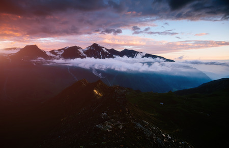 A look at the sunlit hills at twilight. Dramatic evening scene. Location place Grossglockner High Alpine Road, Austria. Europe. Climate change. Popular tourist attraction. Explore the world's beauty. Stock Photo - 120347799