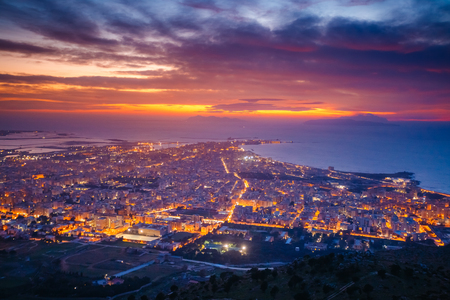 Top view above the city illuminated with lights. Dramatic and picturesque scene. Location place Trapani town, Erice, Sicilia, Italy, Europe. Mediterranean and Tyrrhenian sea. Beauty world.