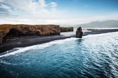 View on Kirkjufjara beach and Arnardrangur cliff. Location Myrdal valley, Atlantic ocean near Vik village, Iceland, Europe. Scenic image of amazing nature landscape. Discover the beauty of earth. Banco de Imagens