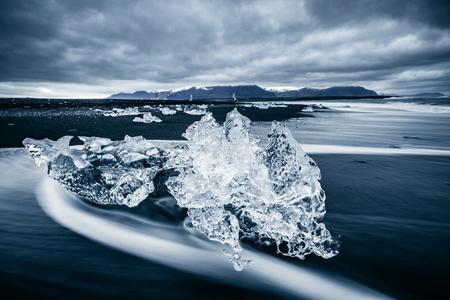 Amazing pieces of the iceberg sparkle on black sand. Location Jokulsarlon lagoon, Diamond beach, Vatnajokull national park, Iceland, Europe. Popular tourist attraction. Discover the beauty of earth. Stock Photo - 123397051
