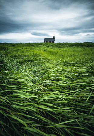 Nice view of Budakirkja christian church. Location hamlet of Budir, Snafellsnes peninsula, Iceland, Europe. Dramatic image of beautiful nature landscape. Moody picture. Discover the beauty of earth.