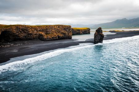 Blick auf den Strand von Kirkjufjara und die Arnardrangur-Klippe. Lage Myrdal-Tal, Atlantik in der Nähe des Dorfes Vik, Island, Europa. Szenisches Bild der erstaunlichen Naturlandschaft. Entdecken Sie die Schönheit der Erde.