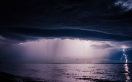 Scenic image of dark ominous clouds. Thunderstorm with lightning. Climate change. Moody weather. Explore the beauty of earth. Picture of wild area.