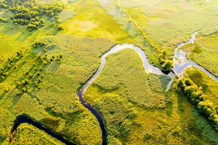 Aerial drone view of winding river in green field. Lush wetlands of birds eye view. Location place countryside of Ukraine, Europe. Textural image of drone photography. Discover the beauty of earth. 스톡 콘텐츠