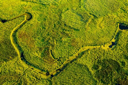 Marvelous view of winding river in green field. Lush wetlands of birds eye view. Location place of Ukraine countryside, Europe. Textural image of drone photography. Discover the beauty of earth. 스톡 콘텐츠