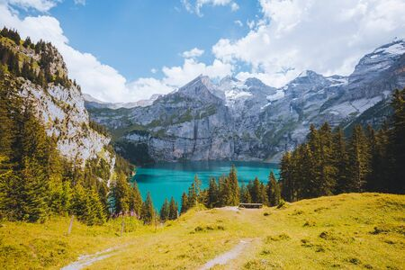 Idyllic panorama view of the azure lake Oeschinensee. Location place Swiss alps, Kandersteg, Bernese Oberland, Europe. Scenic image of most popular tourist attraction. Discover the beauty of earth.