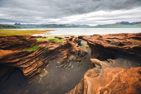 Red sandy rock with by magma formed by wind. Location place Sudurland, cape Dyrholaey, coast of Iceland, Europe. Scenic image of most popular european travel destination. Discover the beauty of earth.