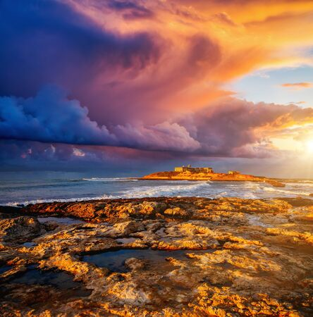 Epic sunset with dark overcast sky. Climate change. Location Island Sicilia, cape Passero, Italy, Europe. Mediterranean sea. Scenic image of popular travel destination. Discover the beauty of earth.