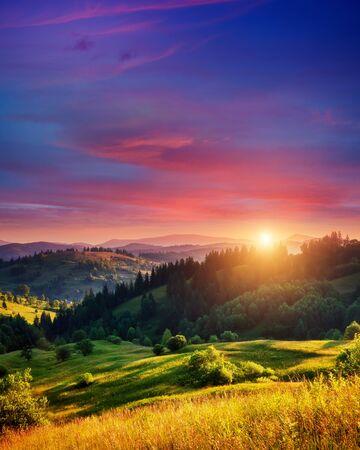 Schöne grüne Hügel, die in der Dämmerung durch warmes Sonnenlicht leuchten. Dramatische Szene. Bunter Himmel, rote Wolken. Karpaten, Ukraine, Europa. Schönheitswelt. Standard-Bild