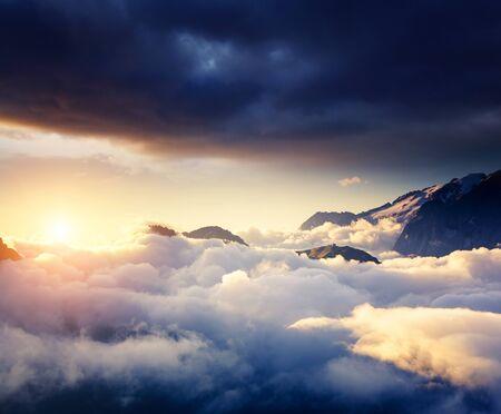 Great view of the foggy Val di Fassa valley with pass Sella. National Park. Dolomites (Dolomiti), South Tyrol. Location Canazei, Campitello, Mazzin. Italy, Europe. Dramatic scene. Beauty world. Stock Photo