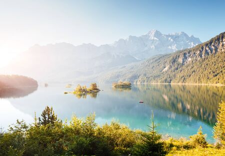 Famous lake Eibsee in the morning light. Location resort Garmisch-Partenkirchen, Bavarian alp, Europe. Scenic image of most popular tourist attraction. Summer wallpaper. Discover the world's beauty.
