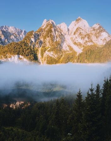 Great morning on the alpine lake Vorderer Gosausee. Picturesque foggy valley. Location place famous resort Salzkammergut, Gosau valley, Austrian alps. Dachstein glacier. Discover the beauty of earth. Banco de Imagens