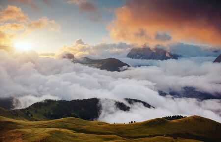 Thick fog covered the ridge in morning. Location place Val di Fassa valley. Scenic image of famous glacier Marmolada, passo Sella, Dolomiti, South Tyrol, Italy, Europe. Explore the beauty of world. Banco de Imagens