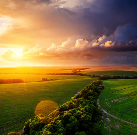 Aerial top view of green rural area under colorful sky at sundown. Location place of Ukraine, Europe. Drone photography. Perfect wallpaper. Concept of agrarian industry. Discover the beauty of world. Standard-Bild - 158709659