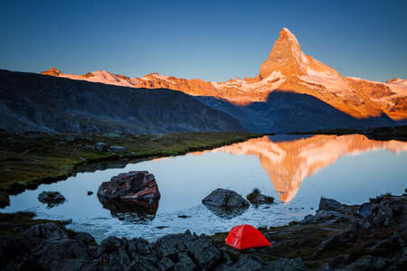 Famous peak Matterhorn (Cervino) in red sunlight. Location place Stellisee lake, Switzerland, Valais region, Swiss alps, Europe. Photo of popular tourist attraction. Discover the beauty of earth. Standard-Bild