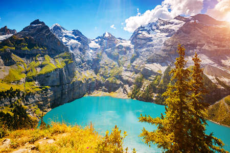 Spectacular view of the lake Oeschinensee in sunny day. Location place Swiss alps, Kandersteg district, Europe. Scenic image of famous landmark. Natural wallpapers. Discover the beauty of earth.
