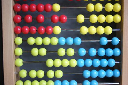 calculating with beads on wooden rainbow abacus for number calculation. Mathematics learning concept