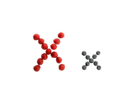 Alphabet X from fresh fruit, raspberry and blackberry, isolated on a white background