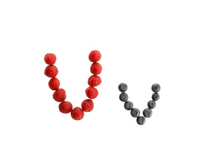 Alphabet V from fresh fruit, raspberry and blackberry, isolated on a white background