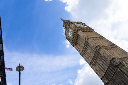 Low angle view of the Big Ben in London England United Kingdom against a blue sky with white clouds and a Union Jack British flag on a building and a streetlight