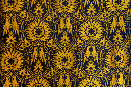 Closeup of a tapestry or fabric patern in gold and black with flowers and birds background backgrop