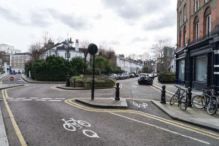 Empty street in Kensington and Chelsea London United Kingdom with houses cars and bikes