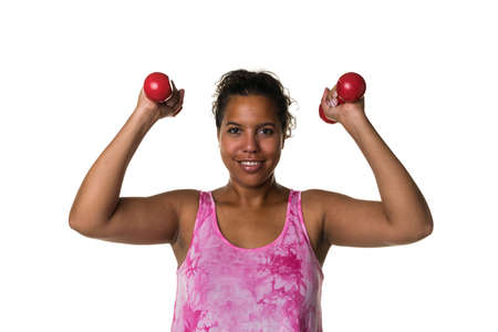 Mixed raced young woman in pink shirt exercising with red 2 kg weights dumbbells isolated in white Stock Photo