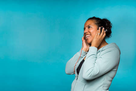 Young attractive mixed race woman enjoying music listening with headphones blue background