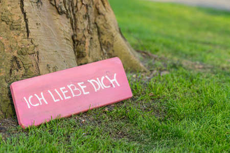 "Pink sign at the foot of a tree saying 'I love you' in German ""Ich liebe dich"""