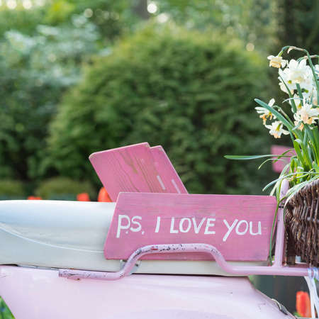 Pink sign on the seat of a scooter saying 'PS I love you'