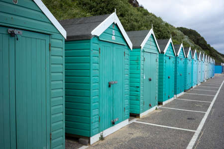 Colorful Beach huts, in green and blue colors, at the boulevard in Bournemouth, Dorset, UK, England on cloudy day in summer
