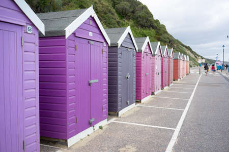 Colorful Beach huts, in purple and pink colors, at the boulevard in Bournemouth, Dorset, UK, England on cloudy day in summer Stock fotó