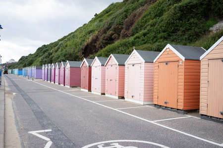 Colorful Beach huts, in orange, peach and pink colors, at the boulevard in Bournemouth, Dorset, UK, England on cloudy day in summer Stock fotó