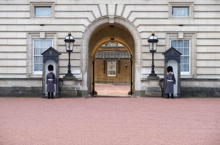 Entrance of Buckingham Palace - England - United Kingdom - with (unrecognizable) Welsh Guards in blue uniform standing guard and seethrough the gate to the inner court on a sunny day