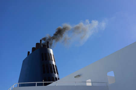 Ferry ship boat chimney detail with dark black smoke concept of enviromental and air pollution by fossil fuel against blue sky
