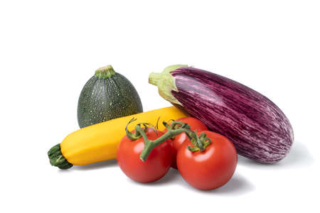 Two variations of zuchinni, tomatoes and an eggplant - ingredients for ratatouille - on a pile seen from under
