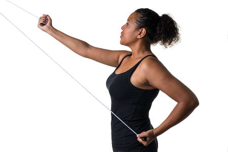 Mixed raced young woman in black shirt exercising with a physiotherapy tool isolated in white
