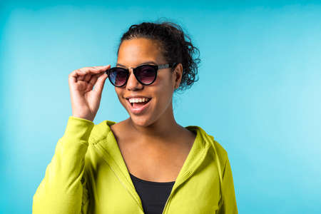 Young attractive mixed race woman with sunglasses in a blue background Stockfoto