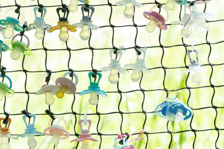Fence with many multicolored pacifiers a place to leave your last pacifier when you've grown up