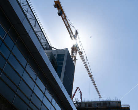 Construction site with tower crane for lifting building materials and the sun in a blue sky Stockfoto