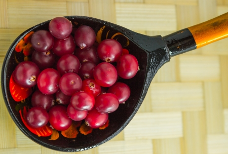 Ripe cranberries, rolled in a wooden spoon  photo