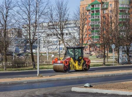 Rink (car) puts asphalt on a sunny afternoon.