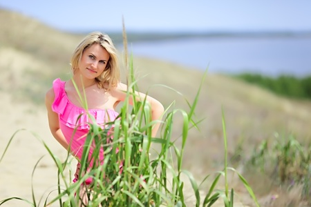 Beautiful blonde in a pink beach costume posing on the dune in a national park Curonian Spit. Stock Photo - 8899204