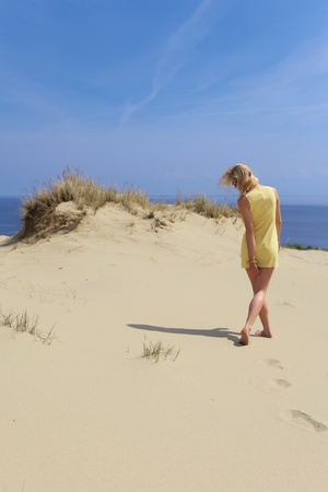 A girl in a yellow dress walking on a sand dune in bare feet, back view   photo