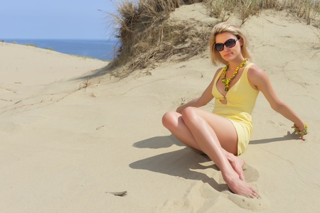 beautiful girl in sunglasses sitting on the sand   photo